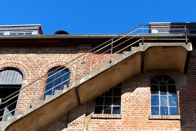 starý cihlový dům a jeho schodiště na boku.jpg